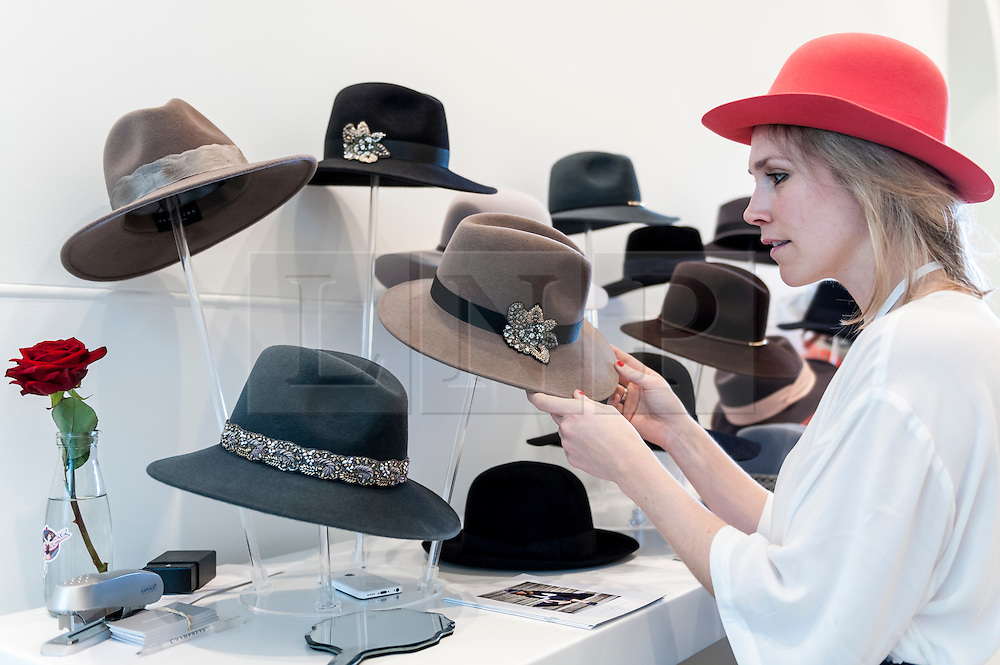 © Licensed to London News Pictures. 22/02/2016. London, UK.  A woman examines hats by Penmayne as Scoop London takes place at the Saatchi Gallery in Chelsea.  Running concurrently with London Fashion Week AW16, the show attracts fashion buyers from around the world who come to meet designers presenting their products amongst the gallery's artworks. Photo credit : Stephen Chung/LNP