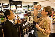 "Two elderly passengers have stopped by in a retail space called World of Duty Free to taste Scottish Malt Whiskey in Terminal 5 at heathrow Airport. The two South-Africans travel widely across the world to visit their extended family and like to stop by this shop to try the various blends of Scotch with the help of a sales person who helps them decide which bottles to buy. Together they swallow the fine alcohol and taste its delicate and subtle differences. From writer Alain de Botton's book project ""A Week at the Airport: A Heathrow Diary"" (2009)."