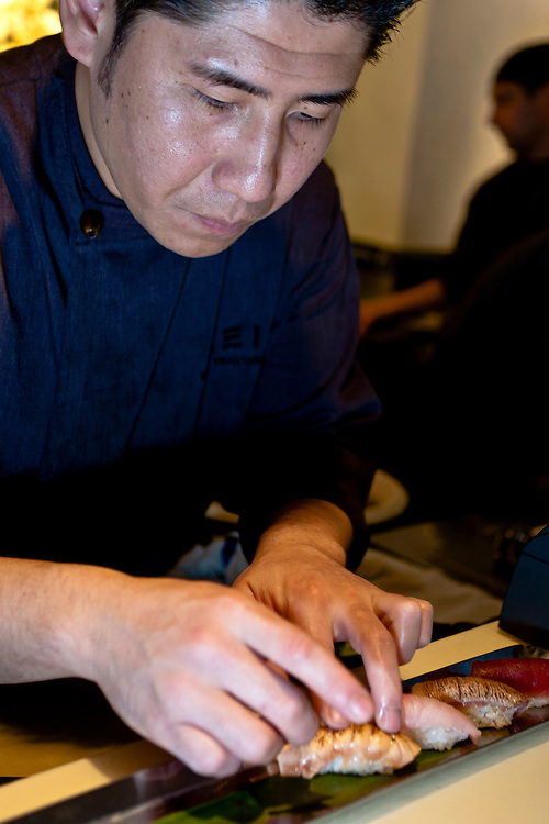 Chef Noriaki Yasutake carefully prepares a piece of sushi.