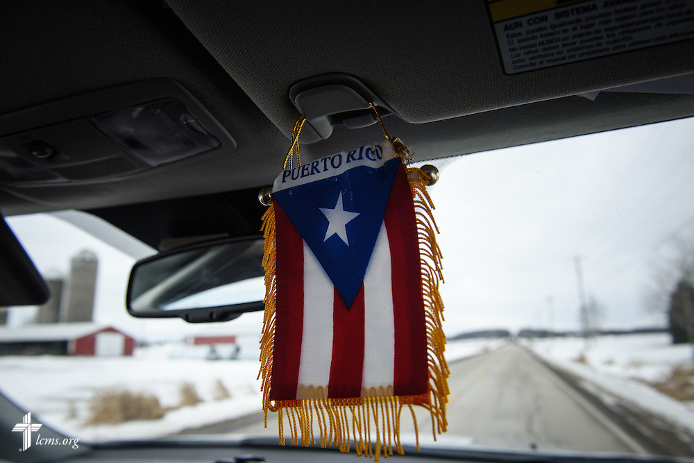 A Puerto Rican flag, pointing to his home roots, dangles from the visor in Vicar David Blas' car as he drives to a farm to build a relationship with the Hispanic employees in rural Random Lake of Sheboygan County, Wis., on Thursday, Jan. 28, 2016. The missionary-at-large at LCMS Sheboygan County Hispanic Outreach and St. John's Lutheran Church of Plymouth, Wis., witnesses in the community as he looks to a growing population of Hispanic residents in the region. LCMS Communications/Erik M. Lunsford