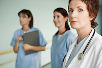 Serious Physician with Nurses in hospital corridor focus on physician portrait
