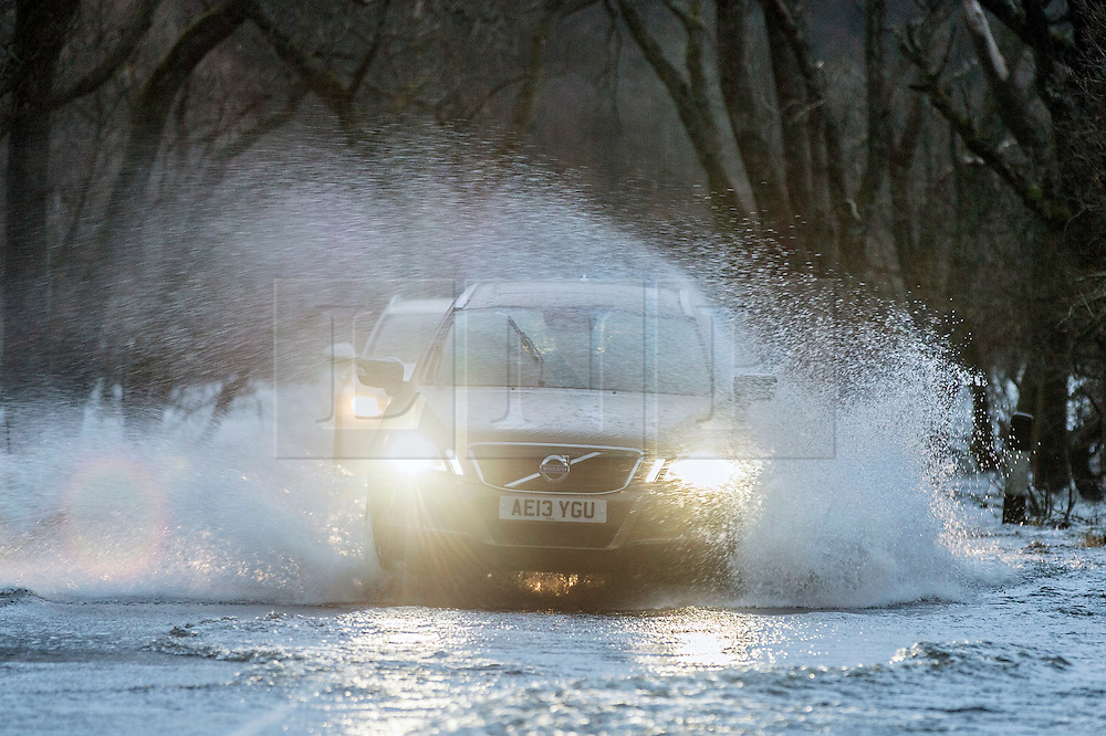 © Licensed to London News Pictures. 30/12/2015. Pooley Bridge UK. Car's struggle through a water logged road in Pooley bridge as Ullswater begins to break it's banks in Cumbria in gale force winds. Photo credit: Andrew McCaren/LNP