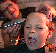 A boy reacts as he has his head-shaving during the annual St. Baldrick's Day head-shaving fundraiser on Thursday, March 14, 2013, in Arcadia, California. More than100 women and men shaved their heads to raises money for child cancer research. The event, ``St. Baldrick's Day,'' is part of a global effort and the world's biggest volunteer-driven fundraising program for childhood cancer. (Photo by Ringo Chiu/PHOTOFORMULA.com).