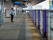 "23 AUGUST 2016 - NONTHABURI, NONTHABURI, THAILAND: A security guard on an empty platform in a station on the ""Purple Line,"" the new Bangkok commuter rail line that runs from Bang Sue, in Bangkok, to Nonthaburi, a large Bangkok suburb. The Purple Line is run by the  Metropolitan Rapid Transit (MRT) which operates Bangkok's subway system. The Purple Line is the fifth light rail mass transit line in Bangkok and is 23 kilometers long. The Purple Line opened on August 6 and so far ridership is below expectations. Only about 20,000 people a day are using the line; officials had estimated as many 70,000 people per day would use the line. The Purple Line was supposed to connect to the MRT's Blue Line, which goes into central Bangkok, but the line was opened before the connection was completed so commuters have to take a shuttle bus or taxi to the Blue Line station. The Thai government has ordered transit officials to come up with plans to increase ridership. Officials are looking at lowering fares and / or improving the connections between the two light rail lines.     PHOTO BY JACK KURTZ"