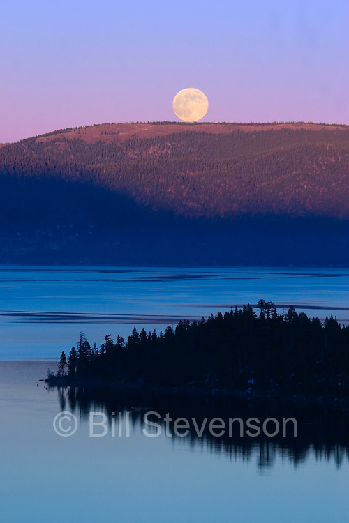 An image of the full moon rising over Lake Tahoe at sunset.