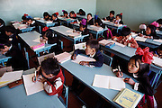 Khorloo Batsuuri (far right) and her fellow students listen to their teacher at school in Ulaanbaatar, Mongolia. The Regzen Batsuuri family lives in a 200 square foot ger (round tent built from canvas, strong poles, and wool felt) on a hillside lot overlooking one of the sprawling valleys that make up Ulaanbaatar, Mongolia. Material World Project.