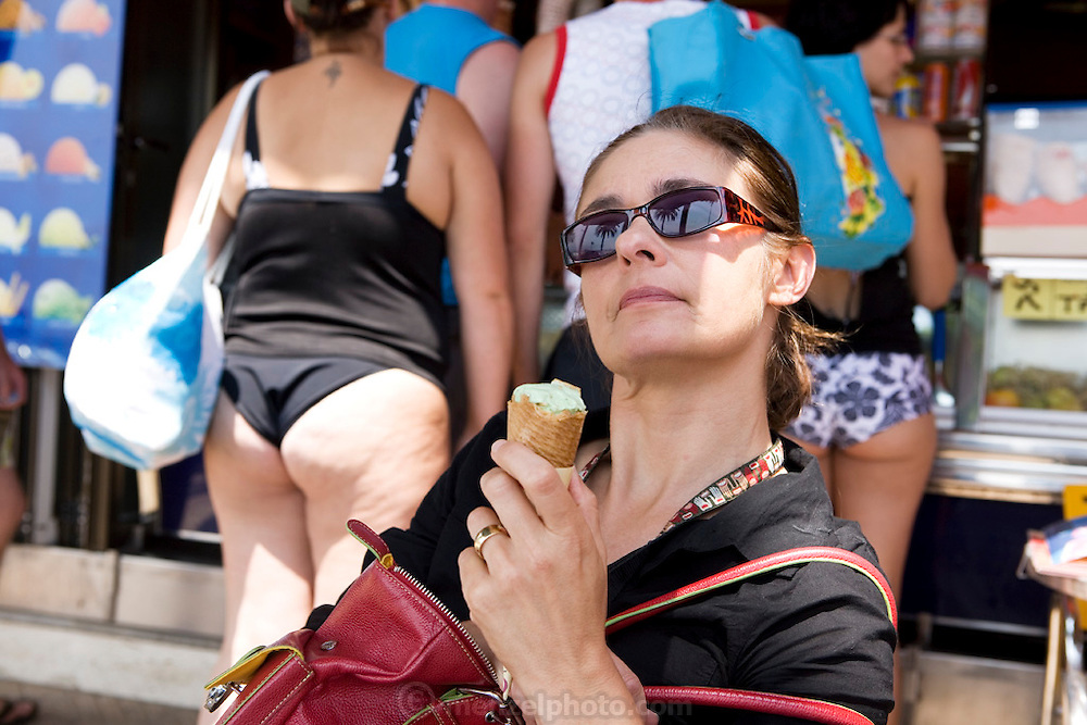 Faith D'Aluisio enjoys a gelatto as some corpulent tourists order theirs in the background. Rosas, Spain.