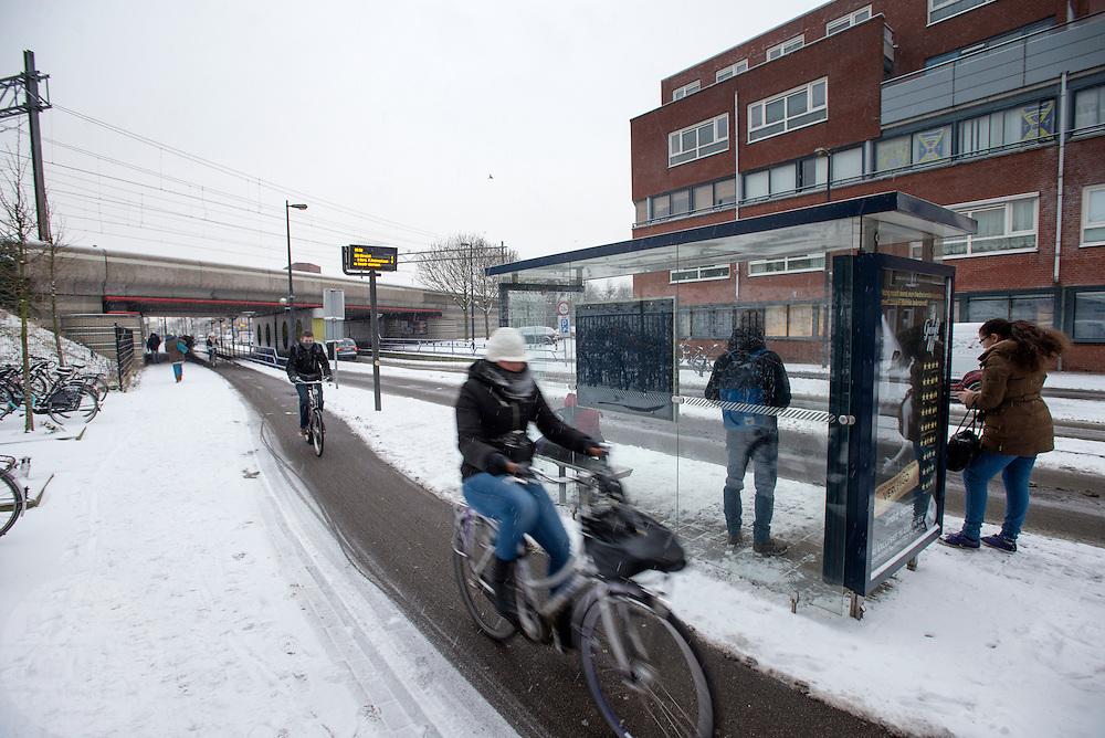 Fietsers rijden door de sneeuw voorbij een bushalte bij de Amsterdamsestraatweg in Utrecht. De eerste sneeuwval van de winter veroorzaakt veel problemen met het verkeer. De gemeente Utrecht heeft de belangrijkste fietspaden wel sneeuwvrij gemaakt.<br /> <br /> Cyclists are passing a bus stop in the snow.