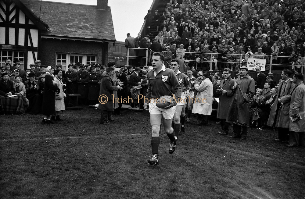Irish team led by team Captain Dawson, enter the field, to play England,..Irish Rugby Football Union, Ireland v England, Five Nations, Landsdowne Road, Dublin, Ireland, Saturday 14th February, 1959,.14.2.1959, 2.14.1959,..Referee- D Gwynne Walters, Welsh Rugby Union, ..Score- Ireland 0 - 3 England, ..Irish Team, ..N J Henderson, Wearing number 15 Irish jersey, Full back, N.I.F.C, Rugby Football Club, Belfast, Northern Ireland,..N H Brophy, Wearing number 14 Irish jersey, Right wing, University College Dublin Rugby Football Club, Dublin, Ireland, ..A J O'Reilly, Wearing number 13 Irish jersey, Right Centre, Old Belvedere Rugby Football Club, Dublin, Ireland, and, Leicester Rugby Football Club, Leicester, England, ..J F Dooley, Wearing  Number 12 Irish jersey, Left Centre, Galwegians Rugby Football Club, Galway, Ireland, ..A C Pedlow, Wearing number 11 Irish jersey, Left wing,  C I Y M S Rugby Football Club, Belfast, Northern Ireland, ..M A English, Wearing number 10 Irish jersey, Outside Half, Bohemians Rugby Football Club, Limerick, Ireland,..A A Mulligan, Wearing number 9 Irish jersey, Scrum Half, London Irish Rugby Football Club, Surrey, England, ..B G Wood, Wearing number 1 Irish jersey, Forward, Garryowen Rugby Football Club, Limerick, Ireland, ..A R Dawson, Wearing number 2 Irish jersey, Captain of the Irish team, Forward, Wanderers Rugby Football Club, Dublin, Ireland, ..S Millar, Wearing number 3 Irish jersey, Forward, Ballymena Rugby Football Club, Antrim, Northern Ireland,..W A Mulcahy, Wearing number 4 Irish jersey, Forward, University College Dublin Rugby Football Club, Dublin, Ireland, ..M G Culliton, Wearing number 5 Irish jersey, Forward, Wanderers Rugby Football Club, Dublin, Ireland, ..N A Murphy, Wearing number 6 Irish jersey, Forward, Cork Constitution Rugby Football Club, Cork, Ireland,..P J A O' Sullivan, Wearing  Number 7 Irish jersey, Forward, Galwegians Rugby Football Club, Galway, Ireland,..J R Kavanagh, Wearing number 8 Irish jersey, Forward