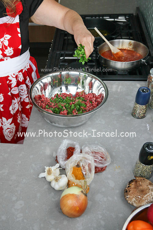 Cooking Moroccan meatballs in tomato sauce adding herbs to the minced meat