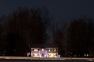 Montgomery, New York  - Headlights from cars streak past a house decorated for Christmas at twilight on Dec. 22, 2013.