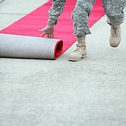 FORT BRAGG, NC  - MARCH 16:  Soldiers literally roll out the red carpet, welcoming troops of the 82nd Combat Aviation Brigade, 82nd Airborne Division, returning to Fort Bragg after a year-long deployment in Afghanistan on March 16, 2010. The unit provided full-spectrum aviation operations in southern Afghanistan and played a key role under heavy fire in the major assault on Marjah last month.