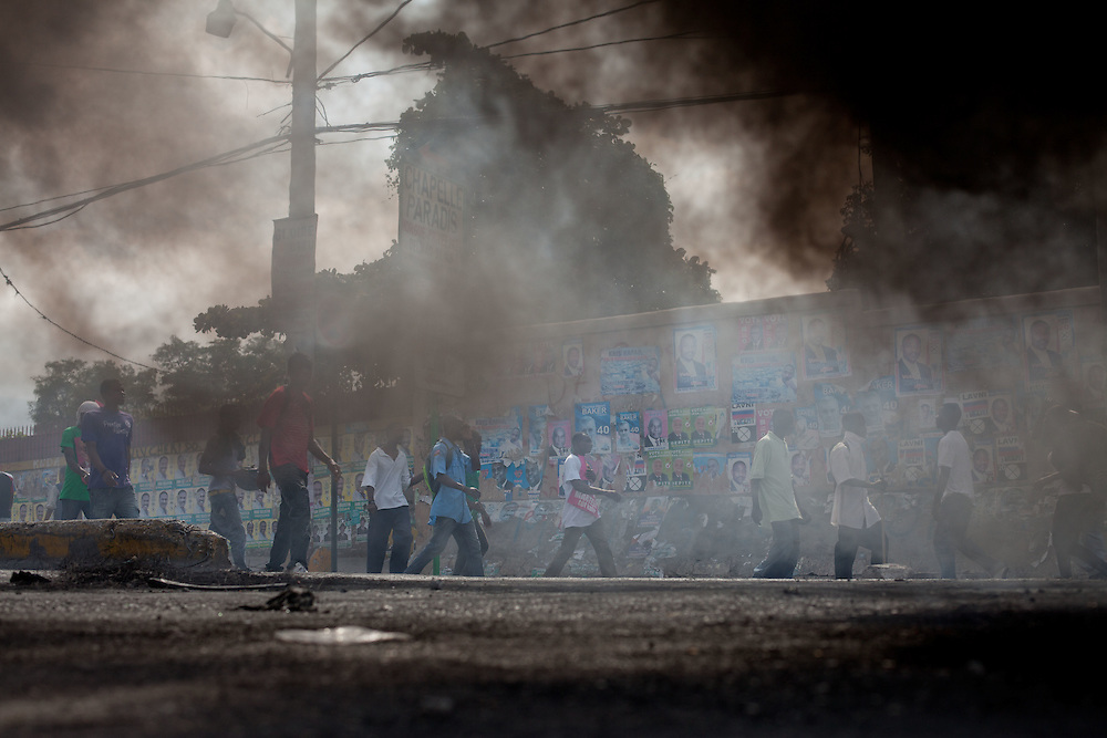 Protesters, many of whom are supporters of Michel Martelly, walk past smoke from burning tires. Protestors take to the streets to protest the results of the January 28th election, which were announced last night.