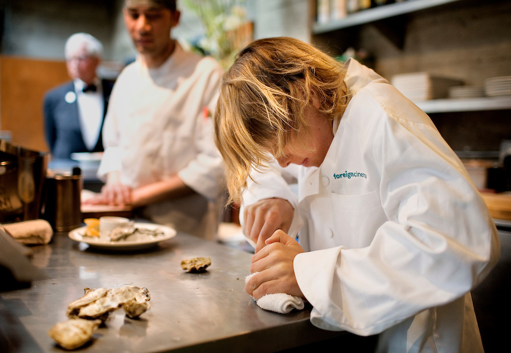 Magnus Pirie-Clark, 10, shucks oysters for his dinner as oyster chef, Al Andrade, keeps an eye on him, at Foreign Cinema, in San Francisco, CA., on Friday, June 12, 2009..