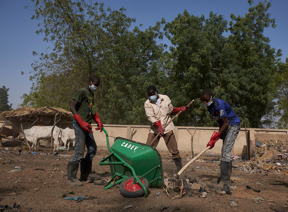 Teenage boys and men collect rubbish as part of a Caritas community activity program in the town of Diffa, Niger on February 12, 2016. 65 men without other means of employment engage in the program collecting rubbish in the streets of various neighbourhoods of Diffa. They participate 10 times per month and are paid 1300 francs (approx. $2) each time. Seen as vulnerable group, especially young men between the age of 14-35 who are susceptible to joining Boko Haram because of no means of earning an income in Diffa, the purpose of the program is the give these men some means of earning money. Many youth after school in the past purchased motorbikes and worked as taxi drivers in the city. With the military banning this in late 2015 because of the frequency of attacks by Boko Haram on motorbikes, approximately 600 who worked in this profession are without jobs. The Caritas staff leading the program undertake awareness campaigns teaching young men about all the damaging effects of the current crisis in the region triggered by Boko Haram.