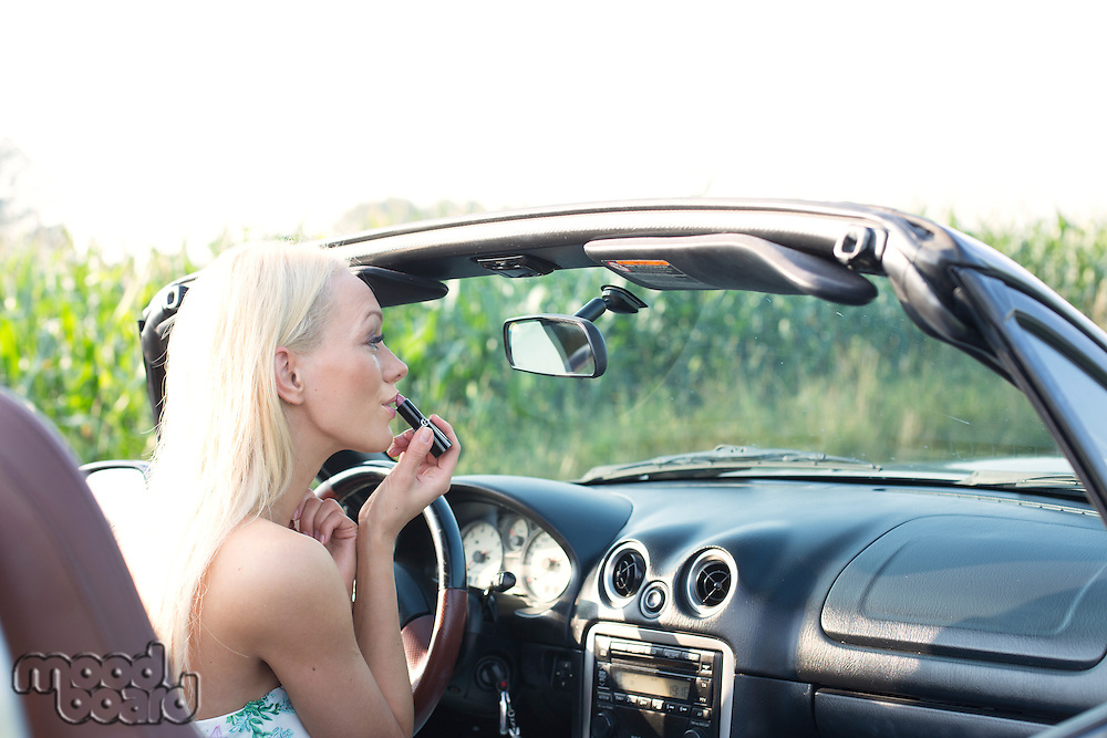 Rear view of woman applying lipstick in convertible