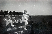 smiling happy children standing by a gate of a farmers field Netherlands 1950s