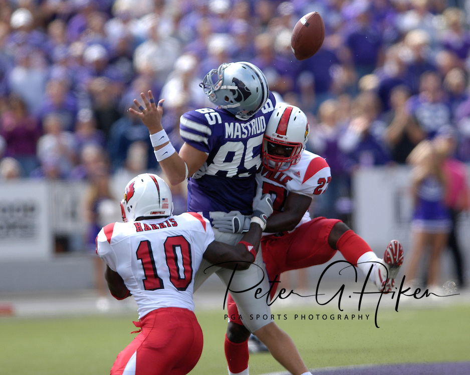 Kansas State tight end Jeron Mustrud (85) has the ball knocked loose after being hit by Louisville defenders Gavin Smart (27) and Nate Harris (10) in the first half, at Bill Snyder Family Stadium in Manhattan, Kansas, September 23, 2006.  The 8th ranked Louisville Cardinals beat K-State 24-6.