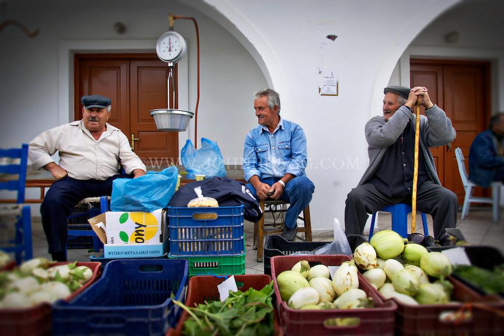 Men selling produce at a market in Santorini, Greece