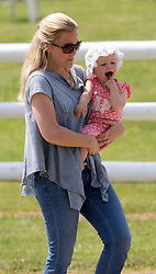 In the picture - Autumn Phillips with daughter Isla.<br /> Peter Phillips the eldest grandchild of Queen Elizabeth II and Prince Philip, Duke of Edinburgh and his wife Autumn Phillips enjoyed a family day out with their children Savannah and Isla at the Barbury International Horse trials, Marlborough, Wilts.  They enjoyed the sunshine whilst watching  Zara Phillips compete in the event.<br /> Marlborough, Wilts, United Kingdom, July 06, 2013. Photo by: i-Images