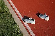 A pair of onely kid-sneakers on sportsground. Ein Paar verlassene Kinderturnschuhe im Sonnenlicht auf Rennbahn. Une paire de sneakers d'enfants solitaire sur un terrain de sport. © Romano P. Riedo