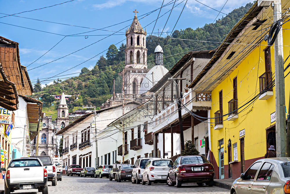 View up Nacional Street toward the Templo de la Inmaculada Concepción church in Angangueo, Michoacan, Mexico. Angangueo is a tiny, remote mountain town and the entry point to the Sierra Chincua Monarch Butterfly Sanctuary.