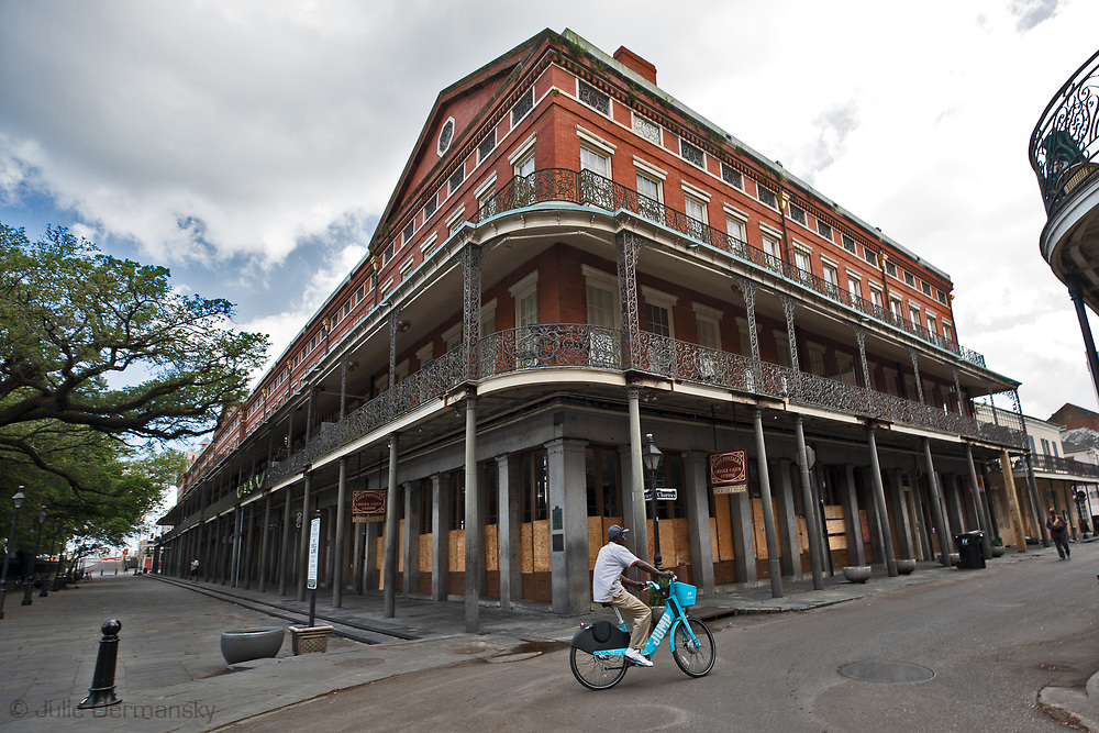 Man on a bike riding by Muriels,, a popular bistro in New Orleans French Quarter on March 27, 2020  during a mandatory stay at home order due to the COVID-19 Pandemic. New Orleans , major city, USA