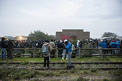 October 24, 2016 - Calais, France - Refugees arriving and waiting at the hangar of distribution of refugees with their luggage. Two refugees are waiting on the railway depot in Calais, France on october 24, 2016. The dismantling of the jungle began Monday morning. Refugees come accompanied by the associations to the starting center ''C.A.O.''. Police frames the device. More than 850 press credentials were distributed. (Credit Image: © Julien Pitinome/NurPhoto via ZUMA Press)