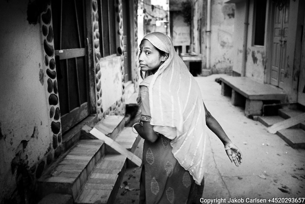 An Untouchable woman working as a manual scavenger goes from house to house in a Caste neighbourhood in Lucknow, India to collect human waste from toilets.