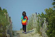 A young girl walks down a path to the beach.