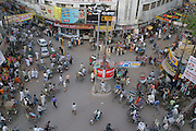An intersection roundabout with a traffic cop in the perpetually busy and noisy streets of Varanasi, India have all kinds of transport. Cows also wander through the city. Varanasi, India..
