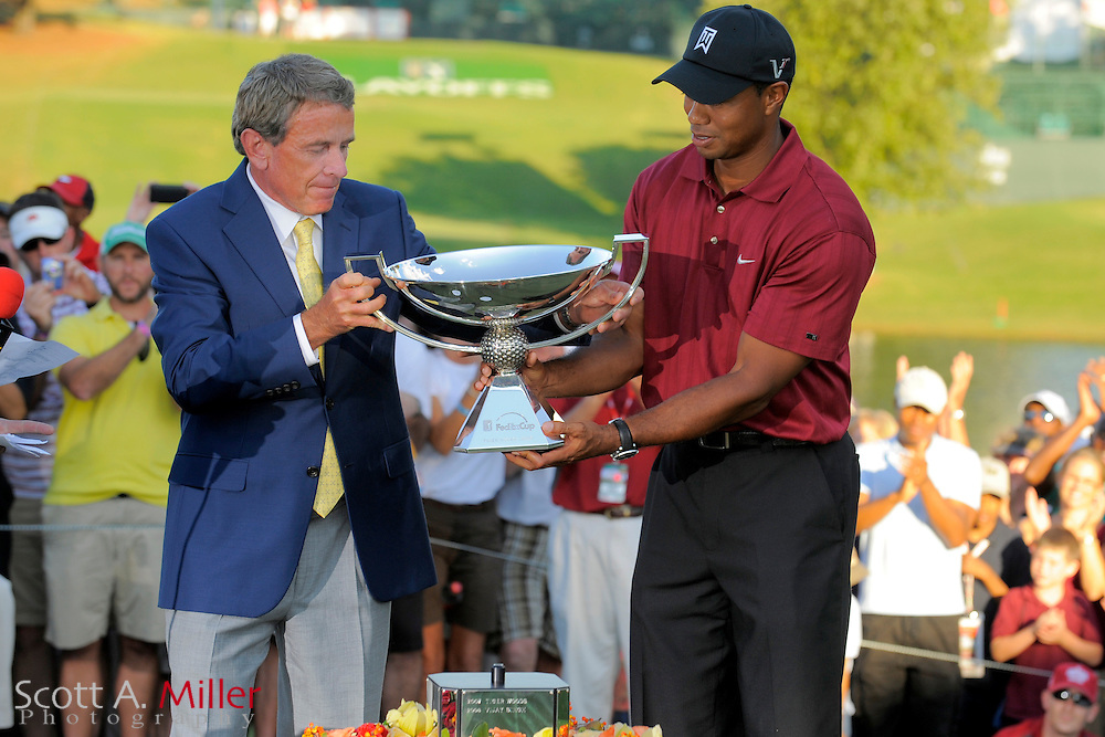 Sep. 27, 2009: Tiger Woods is handed the FedExCup Trophy by PGA Tour commission Tim FInchem following the PGA Tour Championship at East Lake Golf Club in Decatur, Ga...©2009 Scott A. Miller