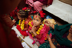 A young Nepalese girl dressed as a living goddess receives gifts during a mass worship on Hanuman Dhoka Durbar Square in Kathmandu.