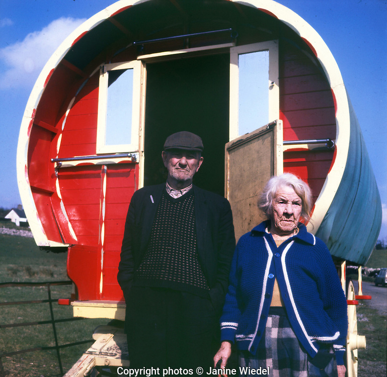 Older Irish Traveller couple infront of their bow shaped readitional wooden caravan in the 1970s