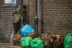 "© Licensed to London News Pictures . Manchester , UK . 05/04/2015 . A couple embrace alongside bagged rubbish, in Manchester's "" Gay Village "" . Revellers on a Saturday night out during the Easter Bank Holiday weekend . Photo credit : Joel Goodman/LNP"