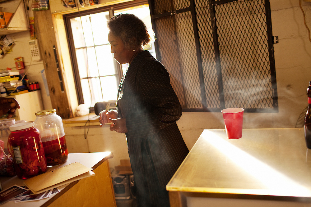 """A woman steps into a shaft of smoky light in Hoover's Convenience Store after the funeral of Demetrius """"Butta"""" Anderson, 18, in the  Baptist Town neighborhood of Greenwood, Mississippi on Friday, November 5, 2010."""