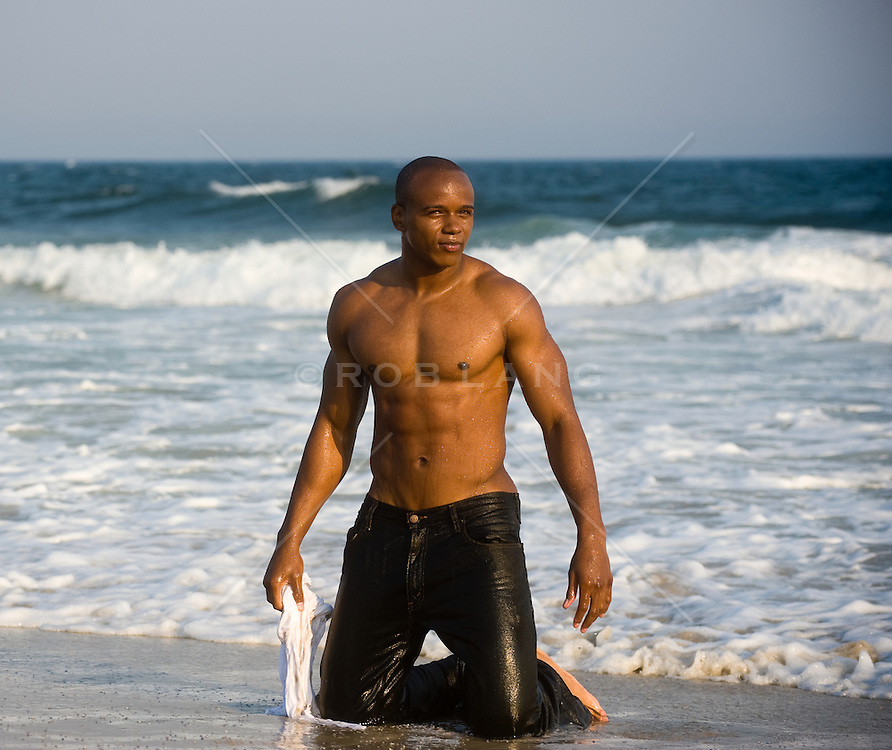 Shirtless young african american man kneeling in the surf in wet jeans