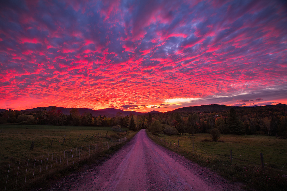 Insanely colorful sunset over a country road near Rochester, Vermont, USA