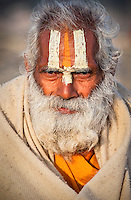 Old man with white paint on face attends kumbh mela religious festival in haradwar, india