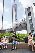 A busker plays guitar Lujiazui district Pudong Shanghai, China