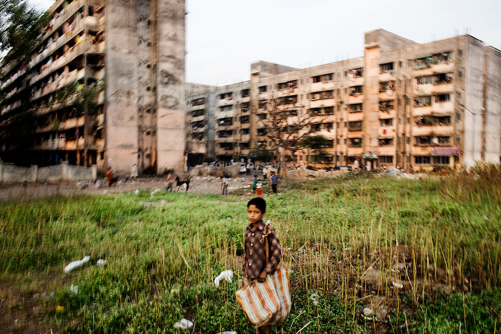 "A small child searches for cans in front of the Lallubhai Compound in Mumbai, 22 November 2009..Mumbai ""slum rehabilitation"" project forced people to move to places like Lallubhai Compound in Mankhurd: 100 building central cluster rises ominously, each building separated from the other by a small corridor full of garbage..More than 60000 people live in this new kind of slum in Mumbai after their homes have been demolished under the claw of a bulldozer.  .Welcome to Mumbai's slum resettlement housing projects, the future of the big metropolis. ."