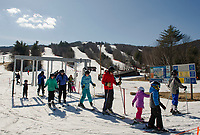 Skiers and riders enjoying the unseasonable warm weather during New Hampshire's school vacation week at Gunstock on Thursday afternoon.  (Karen Bobotas/for the Laconia Daily Sun)