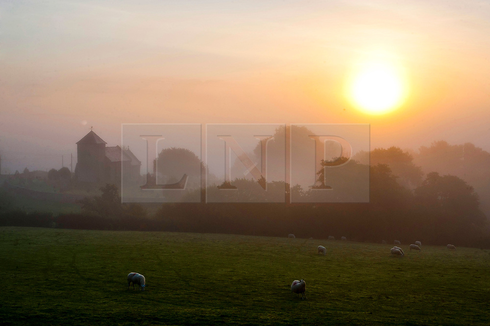 © Licensed to London News Pictures. 30/08/2018. Llanddewi'r Cwm, Powys, Wales, UK. St David's church in the tiny Welsh village of Llanddewi'r Cwm, near Builth Wells in Powys, is surrounded by fog at dawn after a night with temperatures dropping to three degrees centigrade. Photo credit: Graham M. Lawrence/LNP