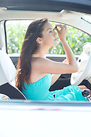 Young woman applying mascara in car