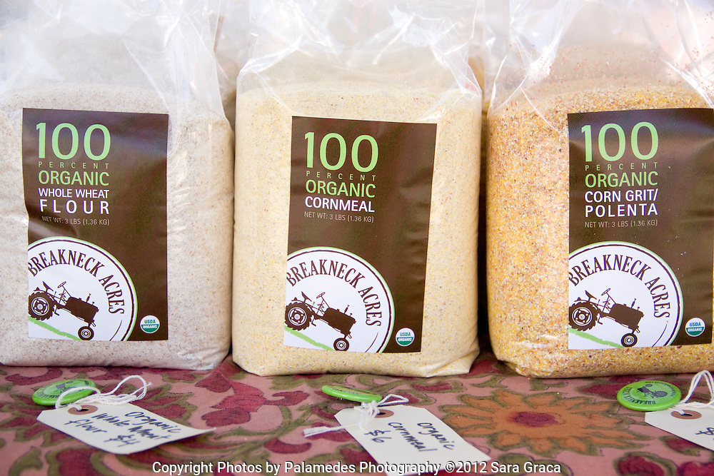 Packages of organic flour, cornmeal and polenta line Breakneck Acre's product table. Other products include corn flour, buckwheat flour, wheat berries and a few varieties of beans.