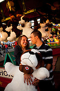A couple celebrates winning a giant stuffed animal during a skill game at the South Carolina Coastal Fair in Charleston, SC.