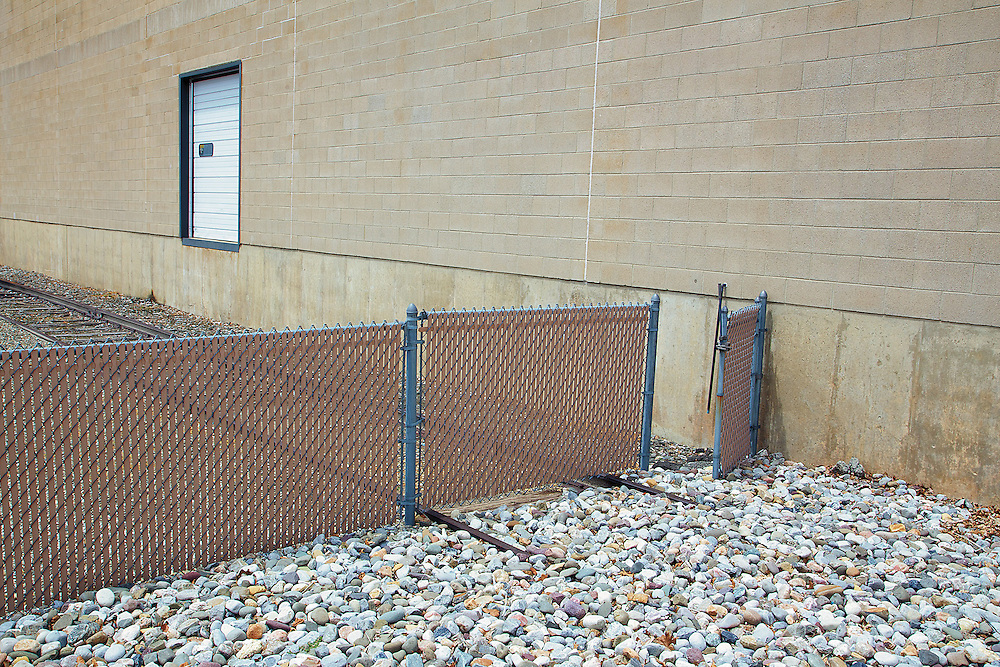 A fence and rocks mark the end of track next to a warehouse.