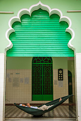 A man takes a nap in a hammock.  amia al Muslimin mosque, Ho Chi Minh city, Vietnam, Asia