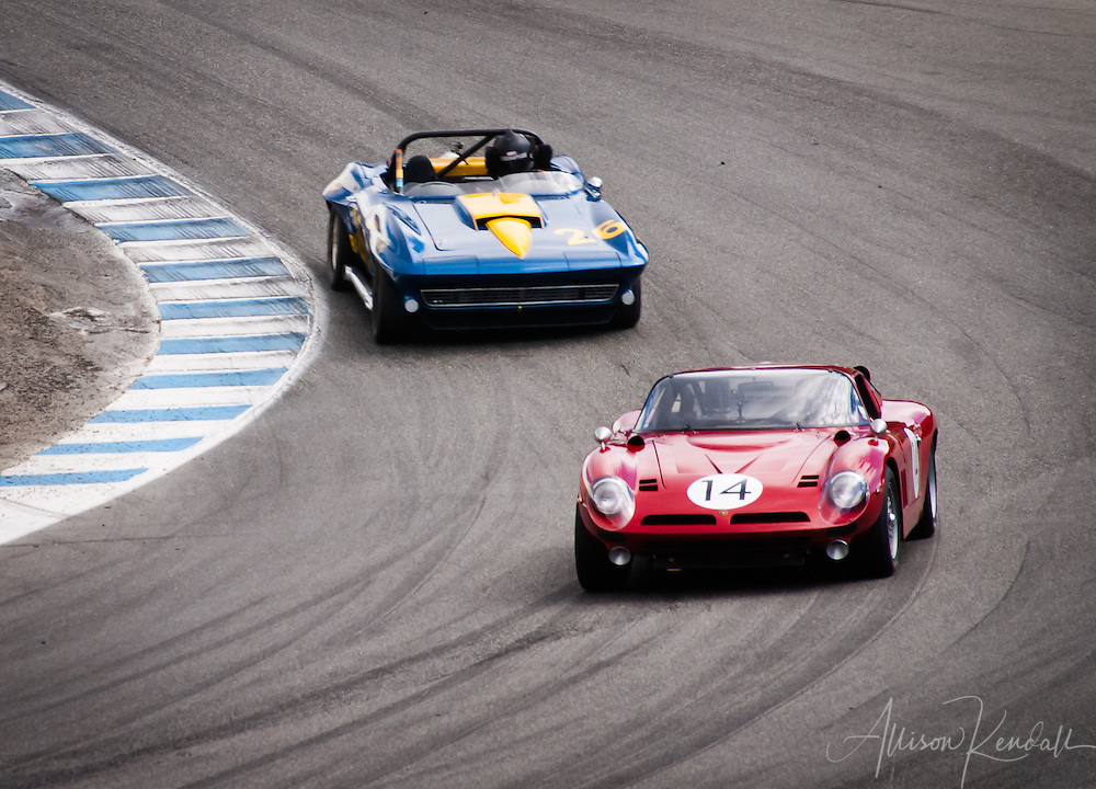 A 1968 Bizzarrini Strada GT driven by John Fudge leads a 1964 Chevrolet Corvette driven by Erickson Shirley through the corkscrew of Laguna Seca at the 2013 Rolex Monterey Motorsports Reunion