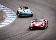 A 1968 Bizzarrini Strada GT driven by John Fudge leads a 1964 Chevrolet Corvette driven by Erickson Shirley through the corkscrew of Laguna Seca, at the Rolex Monterey Motorsports Reunion during Monterey Car Week